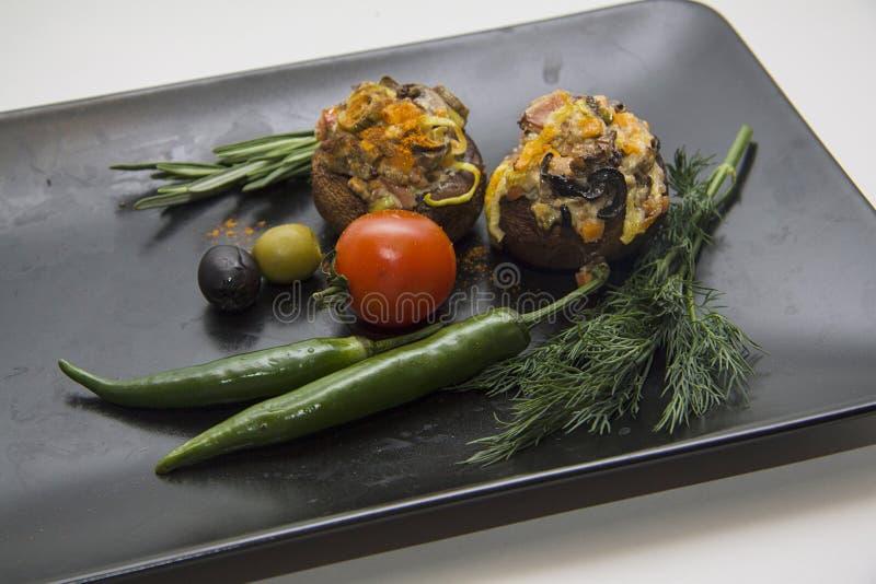 Gevulde champignons met het vullen van close-up op zwarte plaat royalty-vrije stock foto's