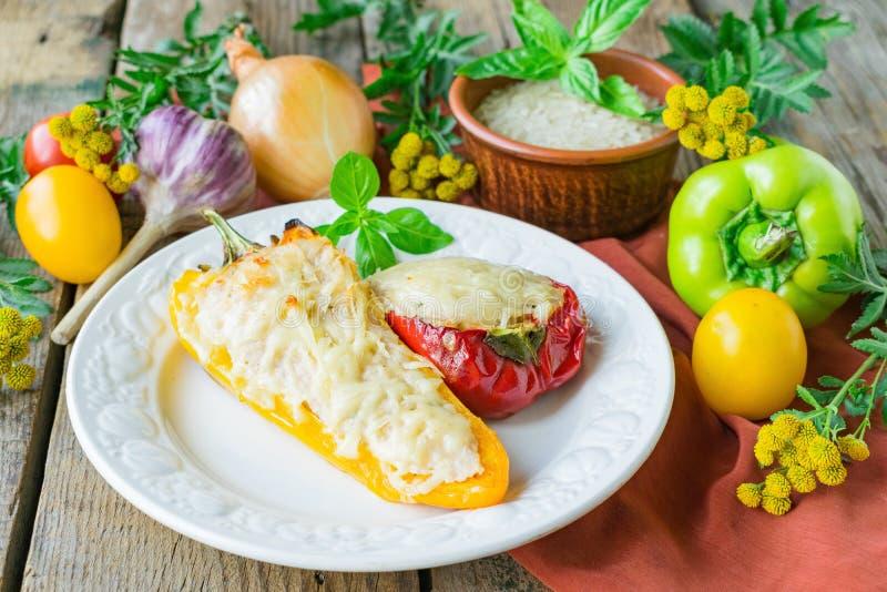 Gevulde die peper met kip en rijst in de oven met kaas wordt gebakken stock afbeeldingen