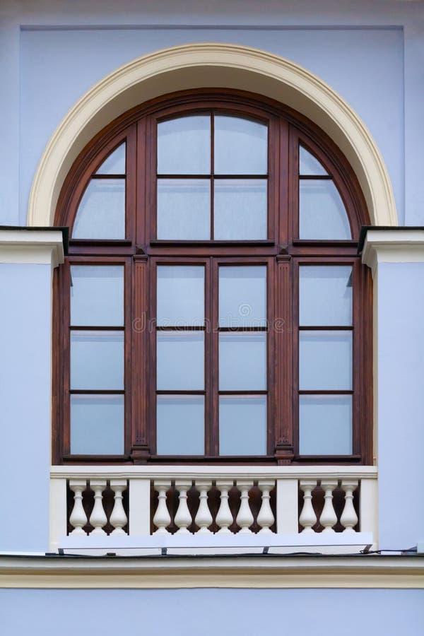 Gewölbtes Fenster mit Holzrahmen und dekorativer weißer Zaun auf Unterseite auf einer Fassade des blauen alten Gebäudes stockbilder