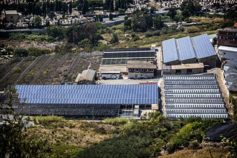 Gewächshaus und Fabrik mit Sonnenkollektoren auf Dach stockfotografie