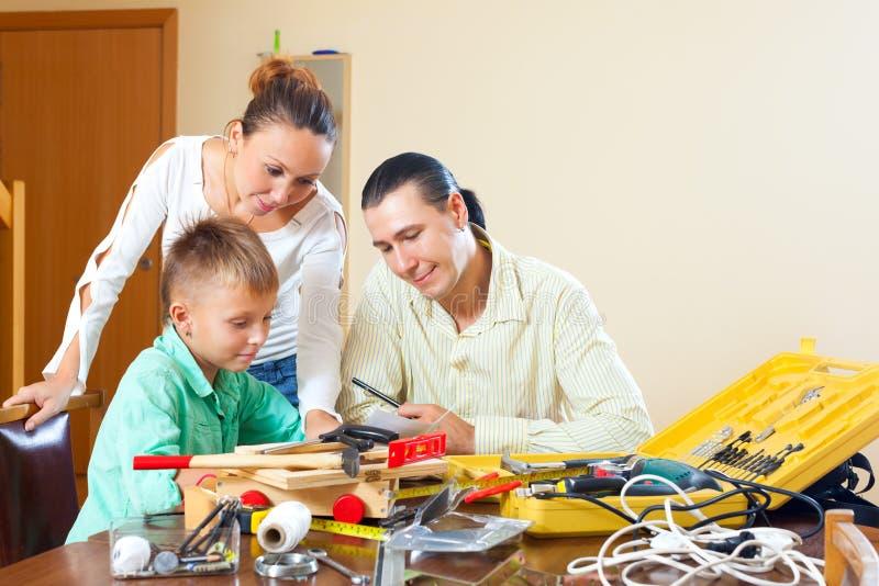 Gewöhnliche dreiköpfige Familie, die etwas mit den Arbeitsgeräten tut stockbild