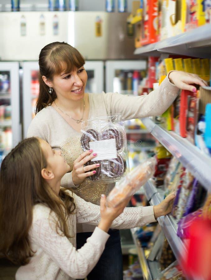 Gewöhnliche Frau und kleines Mädchen, die Bonbons kauft stockfotografie