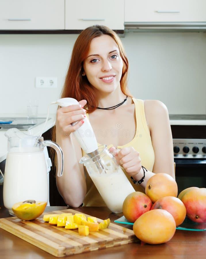 Gewöhnliche junge Frau, die Getränke mit Mischmaschine von der Mango macht stockfoto