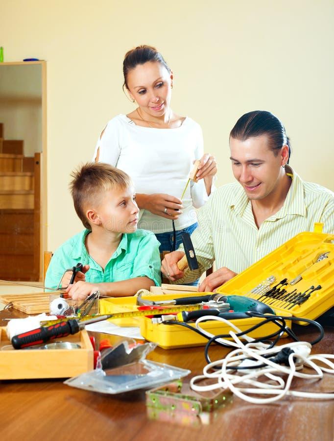 Gewöhnliche nette dreiköpfige Familie, die etwas mit dem Arbeiten macht stockfoto