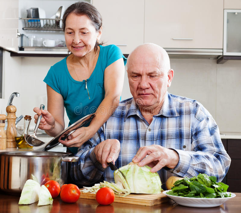 Gewöhnliche reife Paare, die mit Gemüse kochen stockfoto