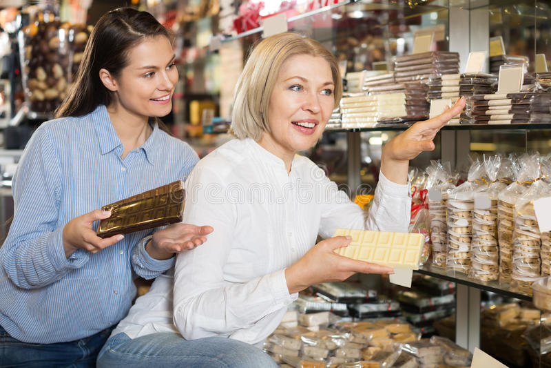 Gewöhnliche weibliche Kunden, die Schokolade vorwählen stockfotografie