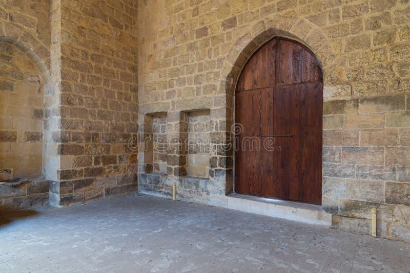 Gewölbte Holztür und zwei eingebettete Nischen in der Steinziegelsteinwand, altes Kairo, Ägypten stockfotografie
