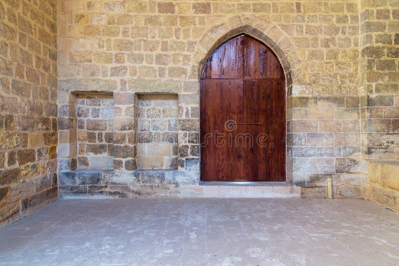 Gewölbte Holztür und zwei eingebettete Nischen in der Steinziegelsteinwand, altes Kairo, Ägypten stockfoto