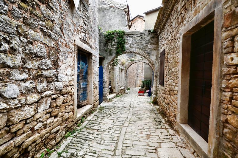 Gewölbte mittelalterliche Straße in einem alten Dorf in Istria, Kroatien stockfotos