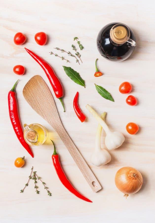 Gewürze und Ölauswahl mit dem Kochen des Löffels auf weißem hölzernem Hintergrund, Draufsicht, Ebenenlage lizenzfreie stockfotos