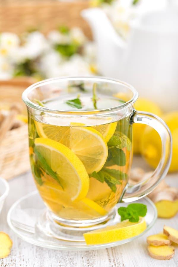 Gewürzter Kräutertee mit frischer Zitrone, Ingwer und tadellosen Blättern auf weißem Hintergrund stockfotos