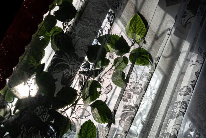 Gew?hnliches Hauptfenster mit transparentem wei?em Tulle und roten Satinvorh?ngen Sonniger heller Tag, Winter drau?en Auf dem Fen lizenzfreie stockbilder