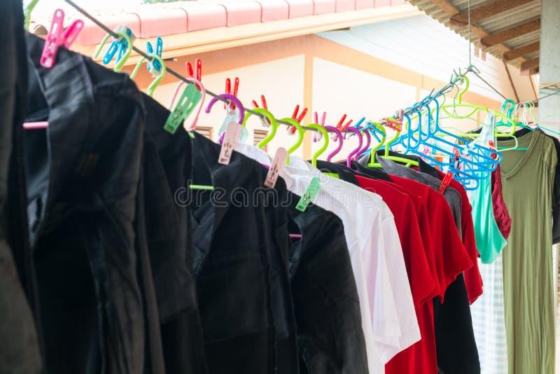 Gewaschene Hose, T-Shirt und Bluse, die am Seil mit Kleidung-Lin hängt stockfoto