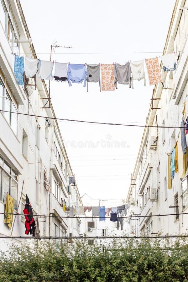 Gewassen kleren die tussen residencial gebouwen in Ayamonte, Spanje hangen royalty-vrije stock fotografie