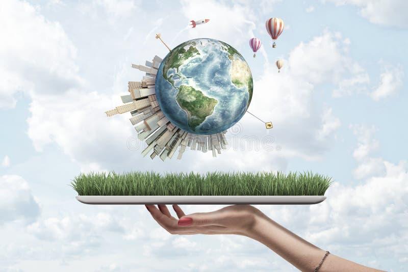 Gewassen zijaanzicht die van de hand van de vrouw digitale tablet met gras op het scherm en weinig Aarde hierboven met wolkenkrab stock foto