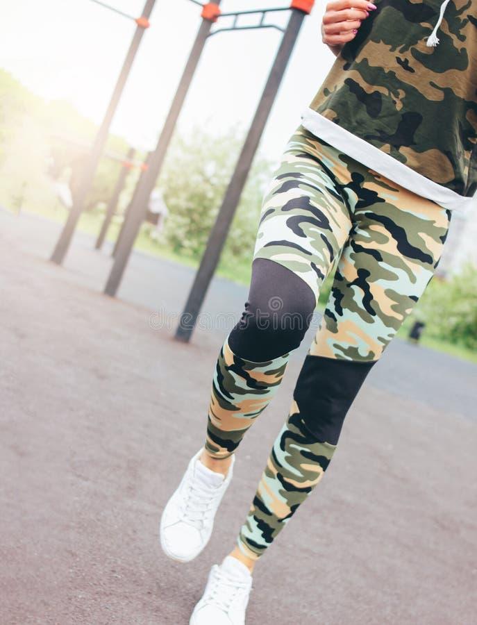 Gewassenfoto van geschikte jonge vrouw in militaire gekleurde sportslijtage die op het gebied van de straattraining lopen De gezo stock foto
