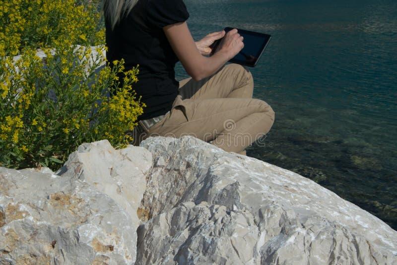Gewassenmening van het jonge volwassen bedrijfsvrouw werken met tabletzitting bij de rand van de kustklip royalty-vrije stock foto's