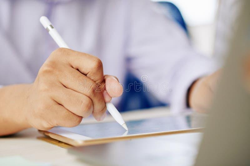 Gewassenmens die aan tablet met naald werken royalty-vrije stock foto