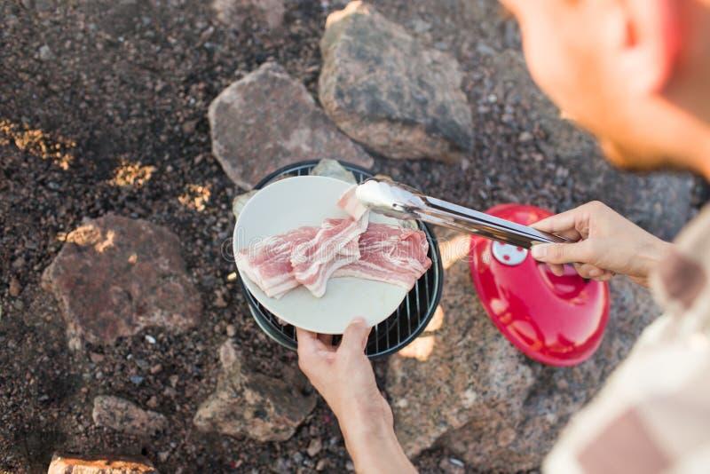 Gewassenpersoon die vlees en bacon roosteren royalty-vrije stock afbeeldingen