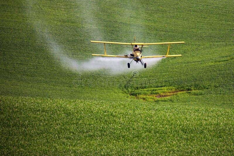 Gewassenstofdoek die een landbouwbedrijfgebied bespuiten stock foto's
