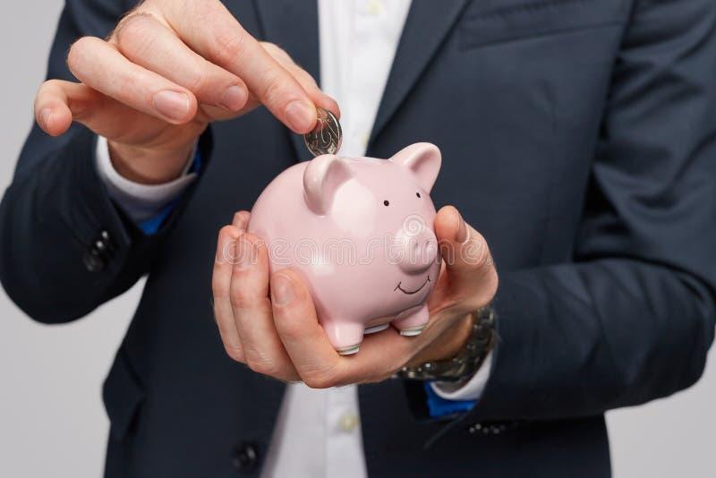 Gewassenzakenman die muntstuk binnen spaarvarken zetten royalty-vrije stock foto's