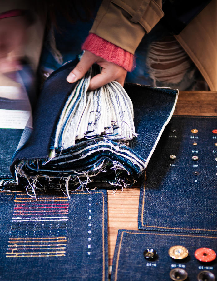 Gewebe Chosing Jean, Jeansniete, Knöpfe, Baumwollstoffschneider, Denim lizenzfreie stockfotografie