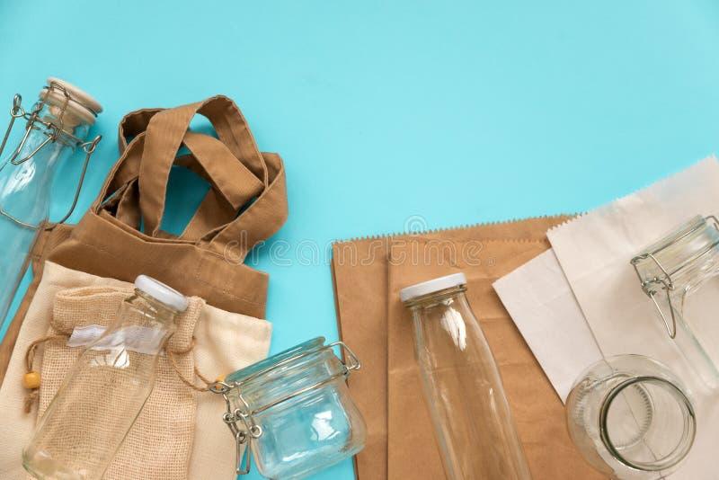 Gewebe-eco Taschen, Papierpakete und Glasgefäße, die auf blauem Hintergrund liegen Eco freundlich, Wiederverwendung oder null übe stockbilder