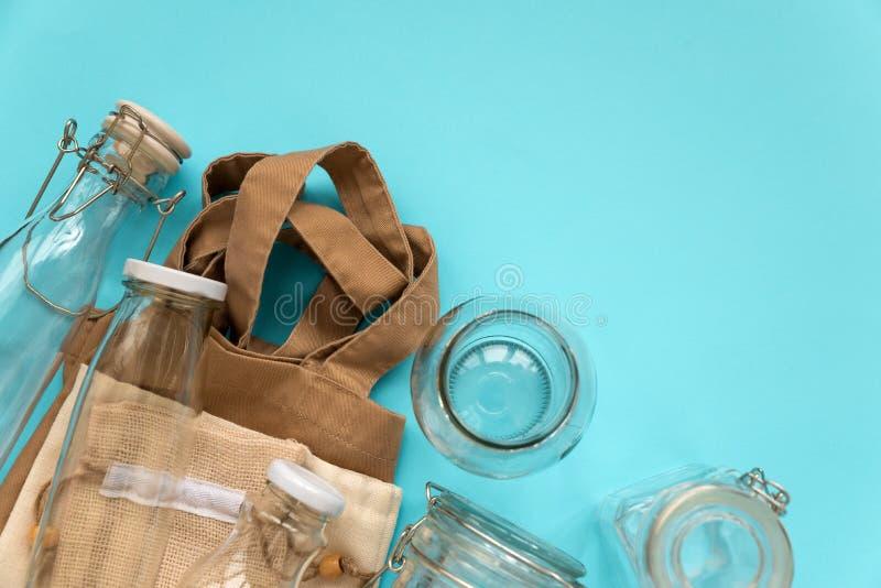 Gewebe-eco Taschen, Papierpakete und Glasgefäße, die auf blauem Hintergrund liegen Eco freundlich, Wiederverwendung oder null übe stockfoto