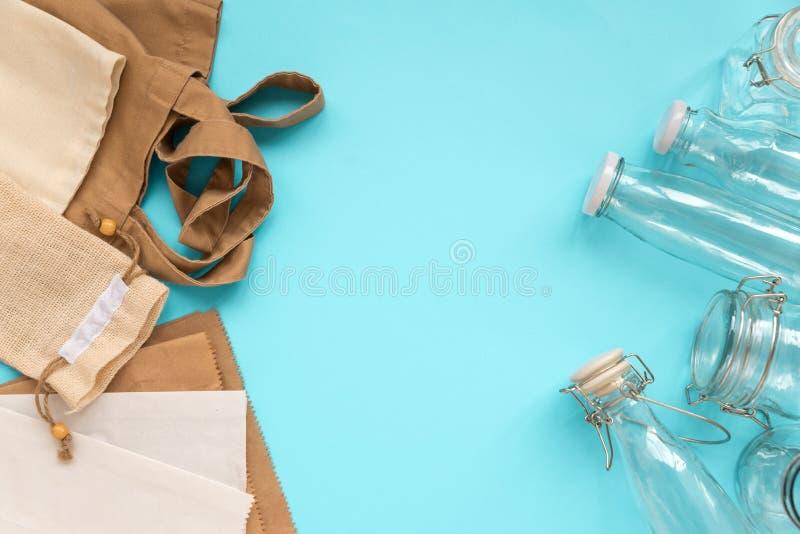 Gewebe-eco Taschen, Papierpakete und Glasgefäße, die auf blauem Hintergrund liegen Eco freundlich, Wiederverwendung oder null übe stockbild