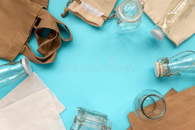 Gewebe-eco Taschen, Papierpakete und Glasgefäße, die auf blauem Hintergrund liegen Eco freundlich, Wiederverwendung oder null übe stockfotos