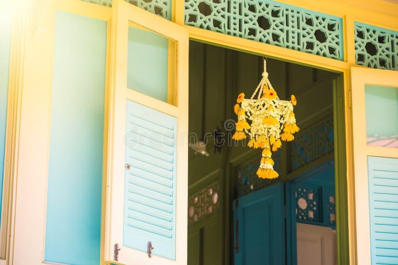 Gewebeblumen, die an den weißen Fenstern antik und an der Retro- Vorhangart bei Thailand hängen stockbild