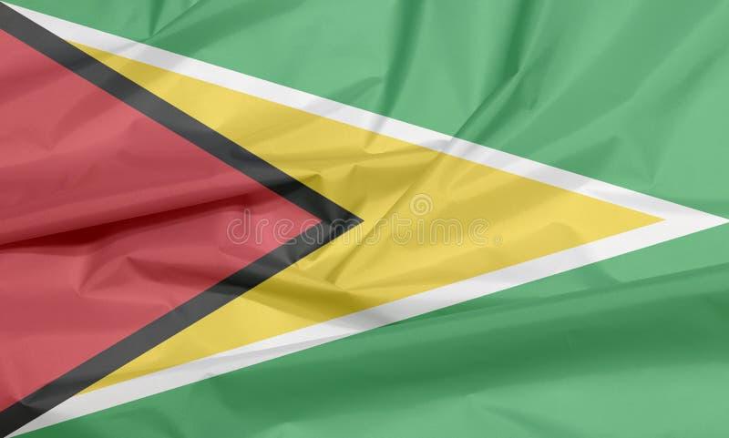 Gewebeflagge von Guyana Falte des guyanischen Flaggenhintergrundes lizenzfreie abbildung