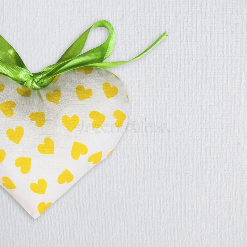 Gewebespielzeugherz auf weißem Segeltuchhintergrund St.-Valentinstag-Postkartenschablone lizenzfreies stockfoto