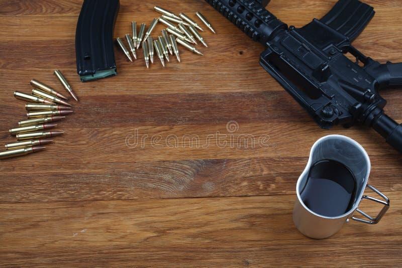 geweer en kop van koffie op houten lijst royalty-vrije stock afbeelding