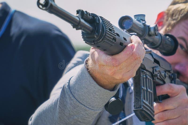 Gewehr mit einem optischen Anblick in den H?nden von M?nnern stockbild