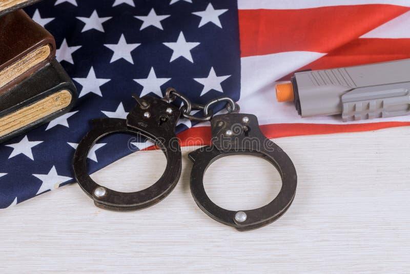 Gewehr und Handschellen auf einer Strafverfolgung der amerikanischen Flagge in den USA lizenzfreie stockfotos