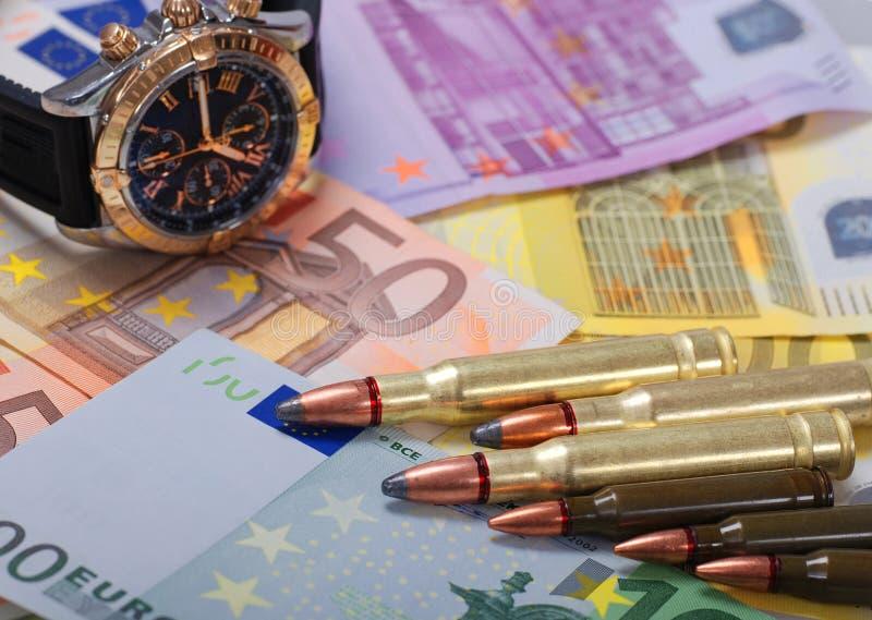 Gewehrkugeln und Uhr auf Eurohintergrund lizenzfreie stockbilder