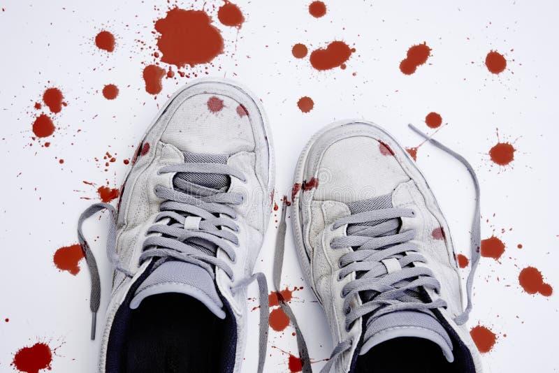 Geweld tegen kinderen Gebruikte met bloed bevlekte tennisschoenen stock afbeeldingen