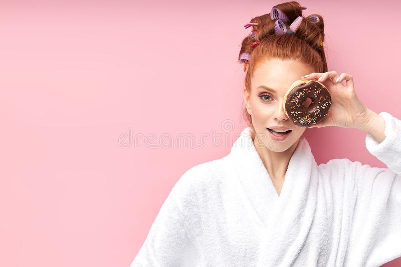 Geweldige kaukasische vrouw met donut poseren boven roze achtergrond stock fotografie