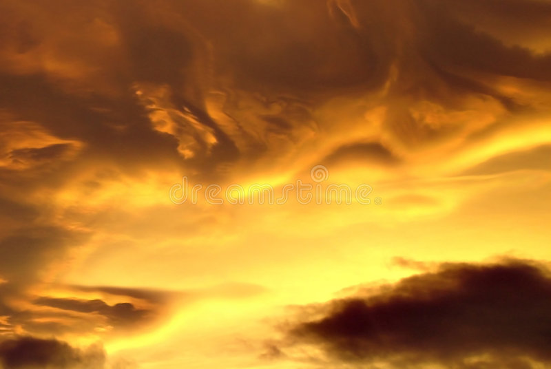 Gewervelde gele en zwarte wolken bij zonsondergang royalty-vrije stock foto's