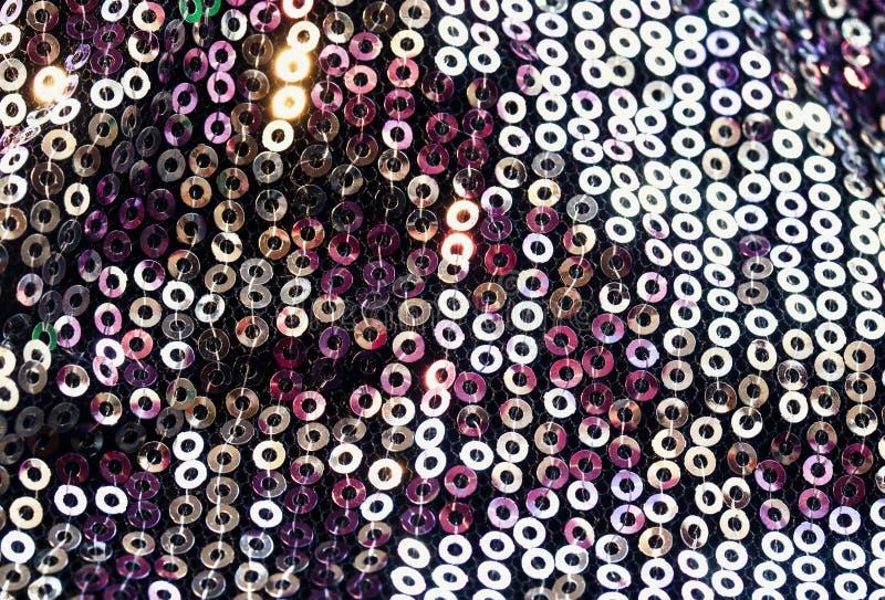 Geweven achtergrond van ronde multicolored iriserende die lovertjes op stof voor een in avondjurk worden genaaid stock afbeelding