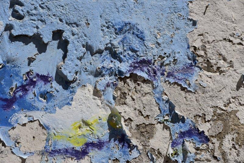 Geweven afschilferende verf - blauwe, groene geel en wit op een grijze muur stock fotografie