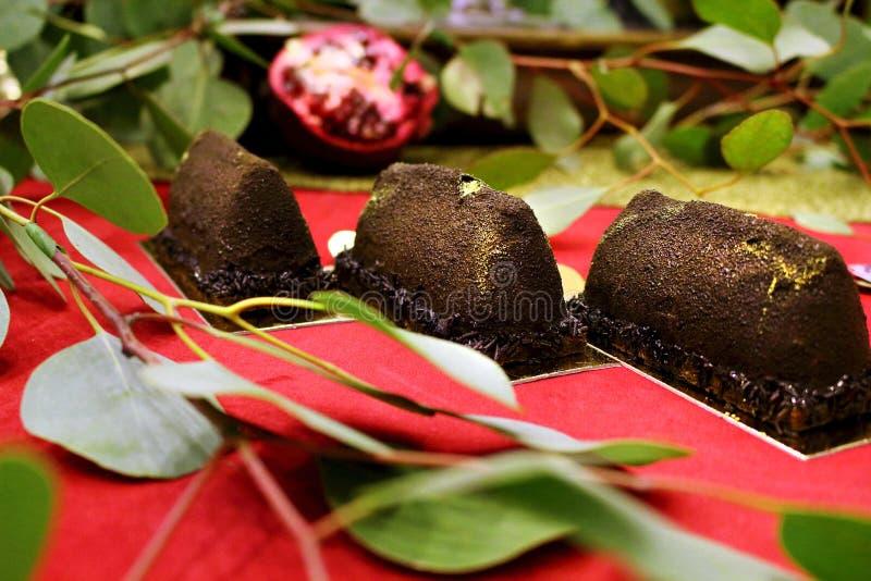 Geweven dessert van het chocolade verlaat het gouden goudklompje op rode het dessertlijst van het tapijthuwelijk met groene eucal royalty-vrije stock afbeeldingen