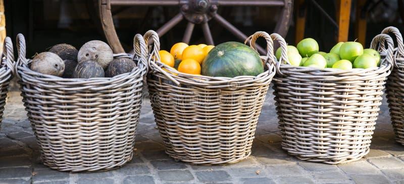 Geweven manden met groene appelen, meloen, sinaasappelen en kokosnoten royalty-vrije stock fotografie