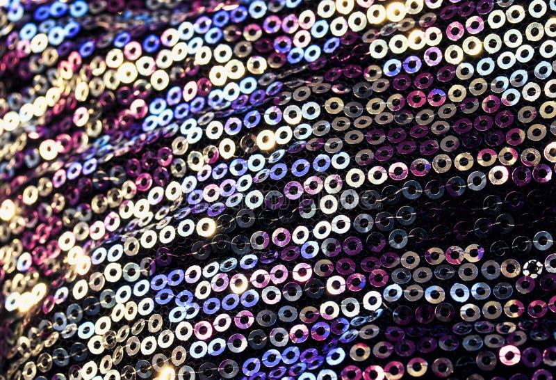 geweven van glanzende ronde multicolored iriserende die lovertjes op stof voor een in avondjurk worden genaaid stock afbeelding