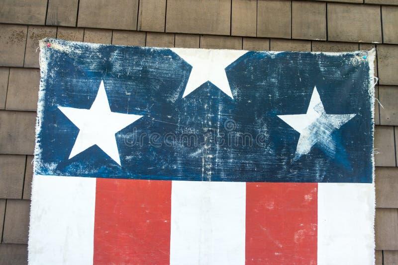 Geweven verontruste hangende Amerikaanse rode witte en blauwe vlag met drie sterren en 5 strepen aan de kant van huismuur 4 Juli royalty-vrije stock foto's