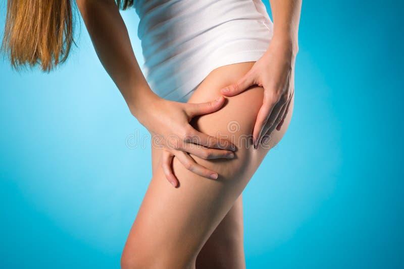 Gewicht lösen - junge Frau, die ihr Bein überprüft stockbild