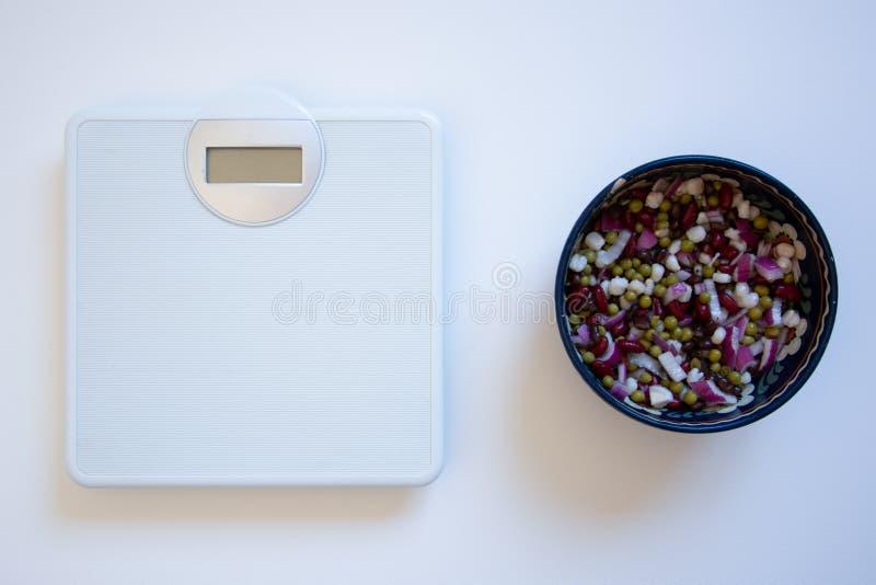 Gewichtsschaal en een kom van bonen en uien royalty-vrije stock afbeelding
