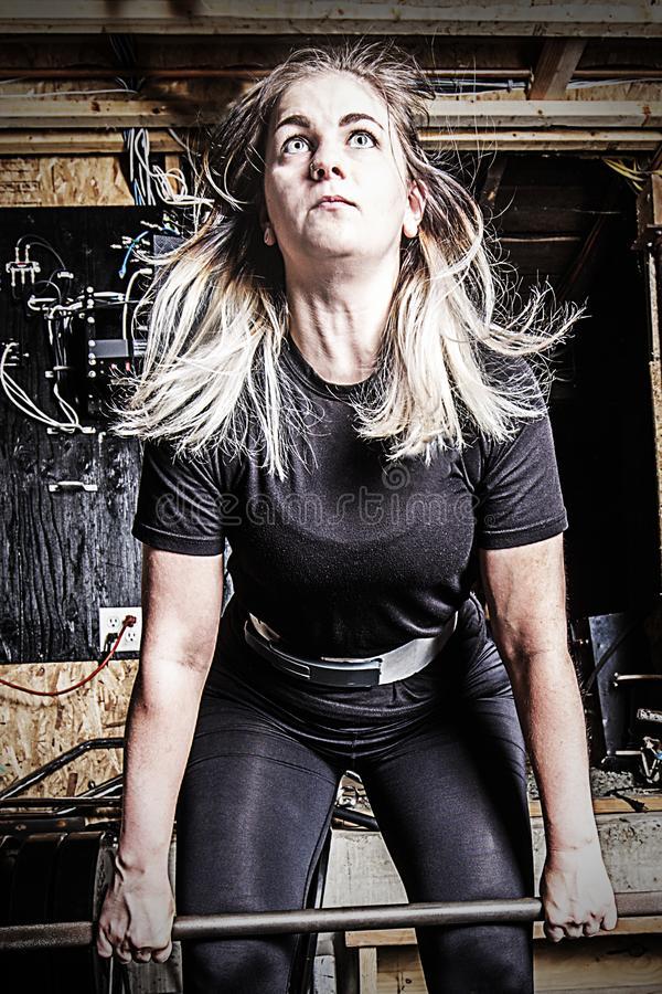 Gewichtstraining der jungen Frau in einer kiesigen Kellerturnhalle lizenzfreie stockbilder