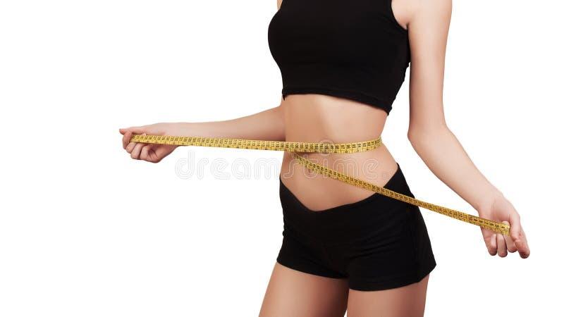 Gewichtsverlies, slank lichaam, gezond levensstijlconcept Geschiktheidsmeisje die haar die taille met maatregelenband meten, op w royalty-vrije stock afbeeldingen